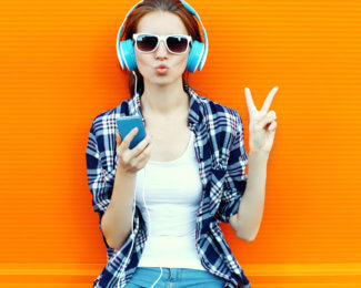 Pretty cool girl having fun and listens to music in the headphones on smartphone over colorful background