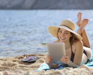 Pretty woman reading a tablet reader on vacations